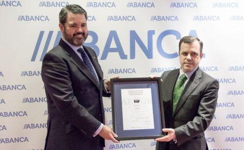 Luis Beraza de Diego, director xeral de negocio España de Abanca, y Ramón Palacios, gerente de excelencia, banca y servicios de Aenor, muestran la certificación en la sede de la entidad en A Coruña