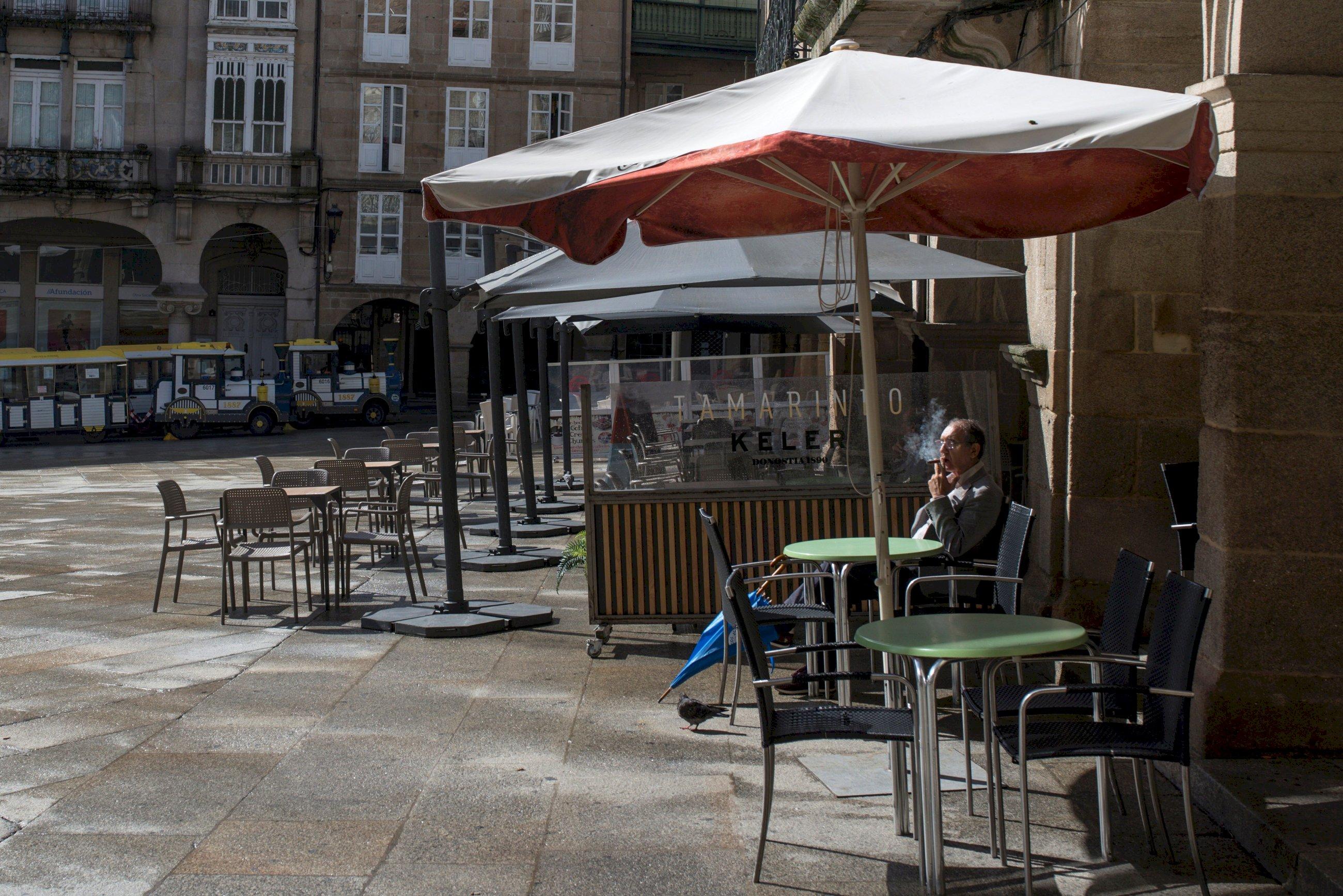 Un hombre fuma en la terraza de un bar