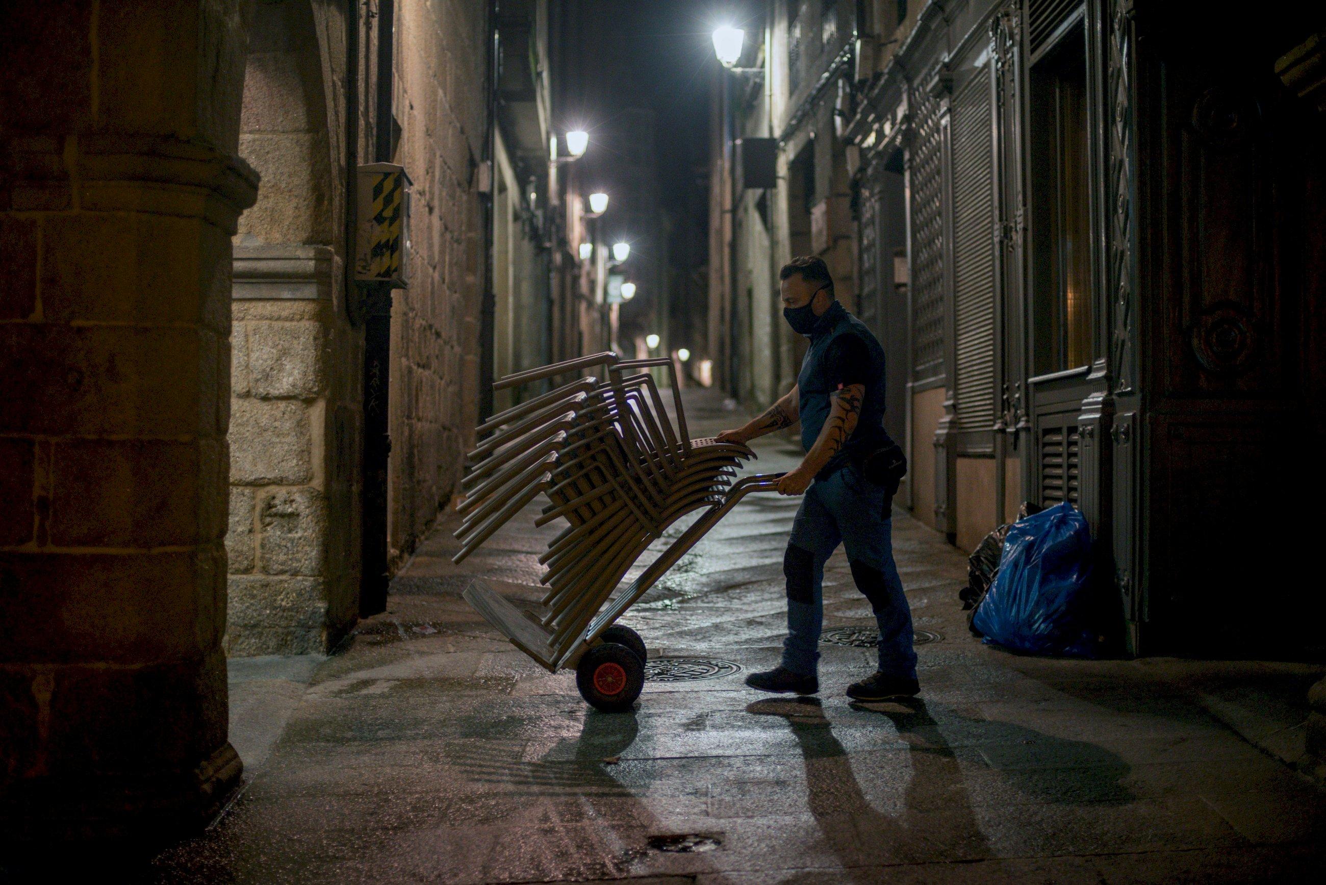 Un hombre recoge las sillas de una terraza / EFE