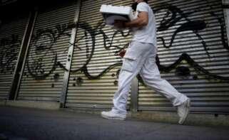 Un trabajador pasa por delante de un comercio cerrado en A Coruña