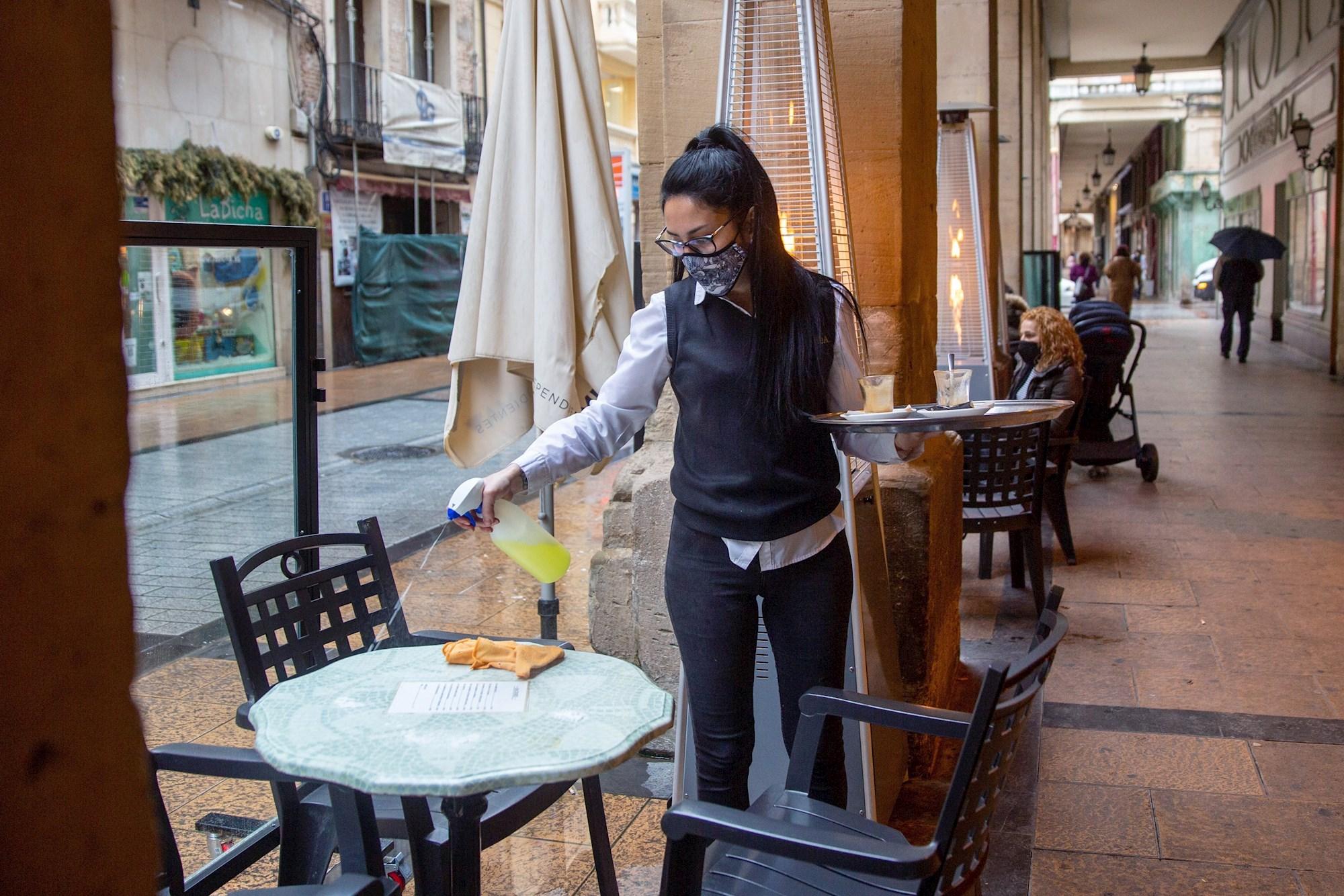 Una camarera desinfecta una mesa