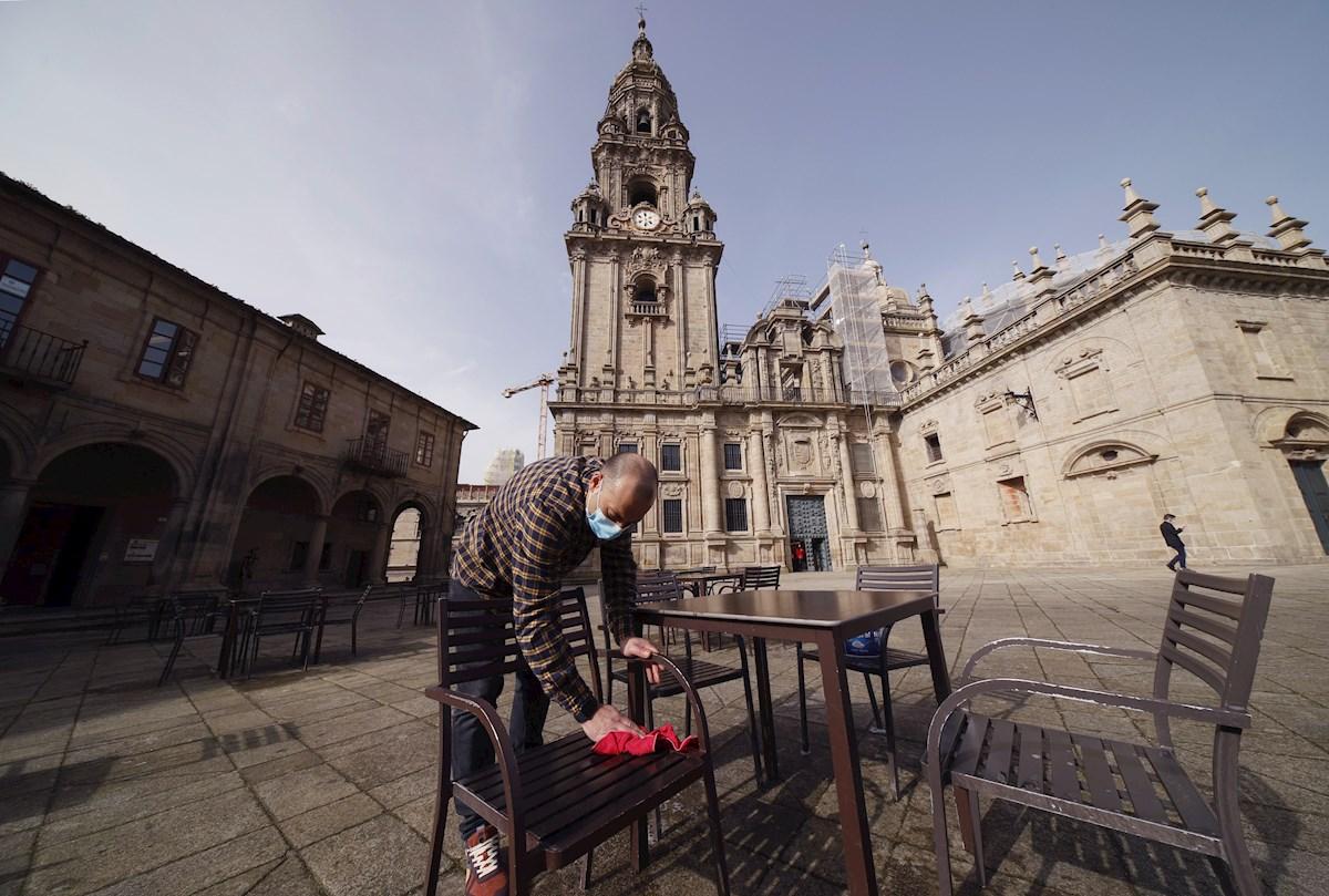 Un hostelero prepara la terraza en la plaza de A Quintana, en Santiago de Compostela. EFE/Lavandeira jr