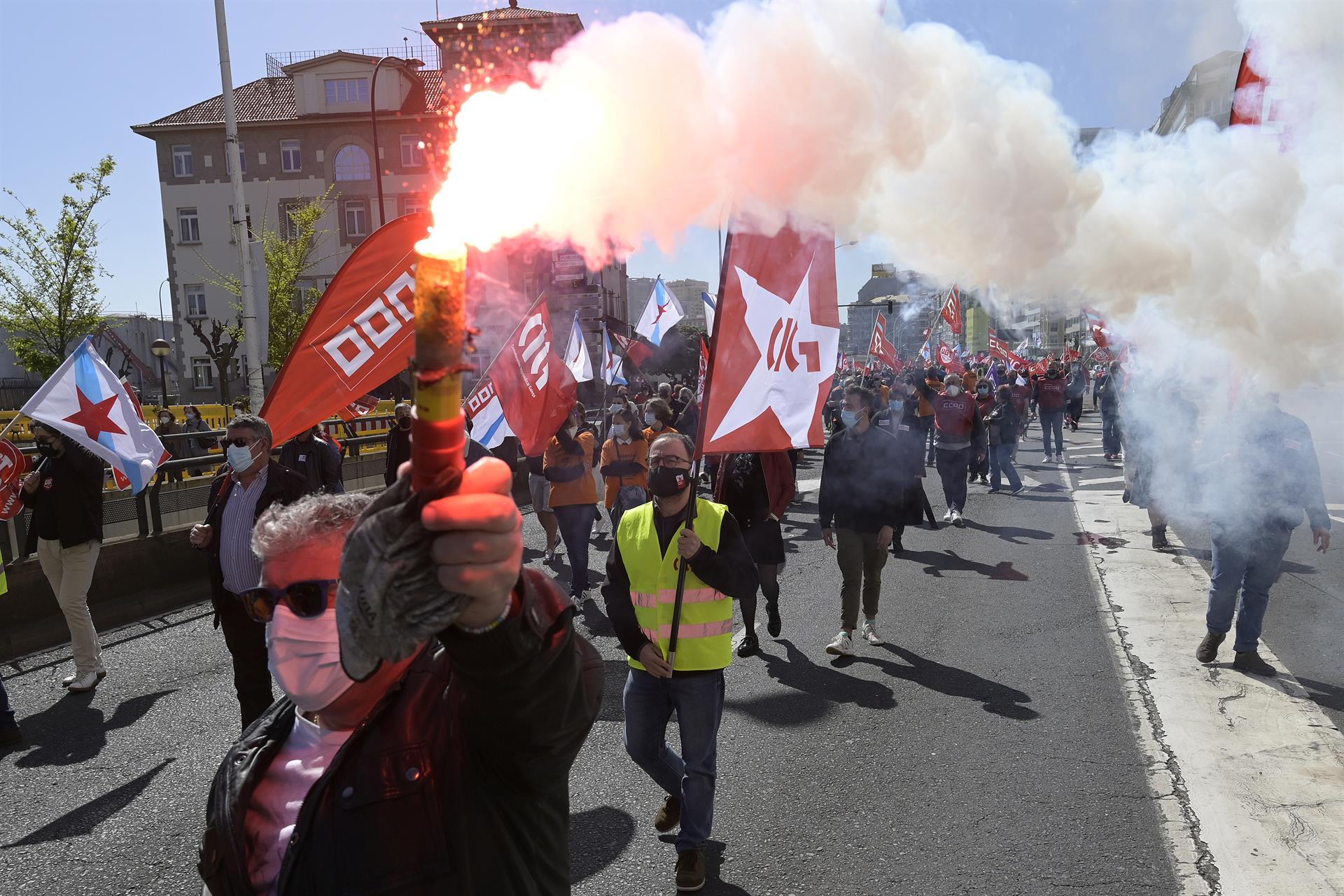 """Decenas de personas con banderas de sindicatos y humo durante una manifestación convocada por varios sindicatos""""en defensa del empleo, por un futuro industrial, contra la represión sindical en Alu Ibérica"""" en la plaza de Ourense de A Coruña. - M. Dylan - Europa Press"""