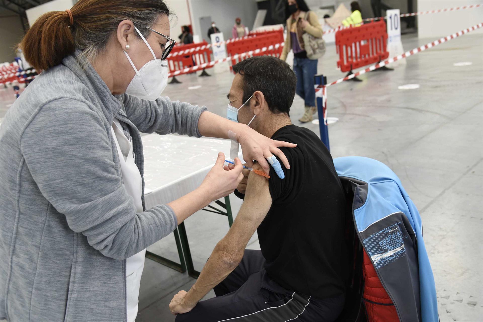 Una sanitaria vacuna a una hombre en el Instituto Ferial de Vigo (Ifevi), en Pontevedra, Galicia (España), a 13 de marzo de 2021