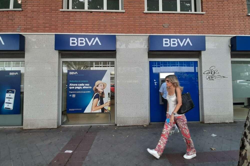Una mujer pasa una oficina bancaria con el nuevo logo del BBVA en Madrid. - Eduardo Parra - Europa Press - Archivo