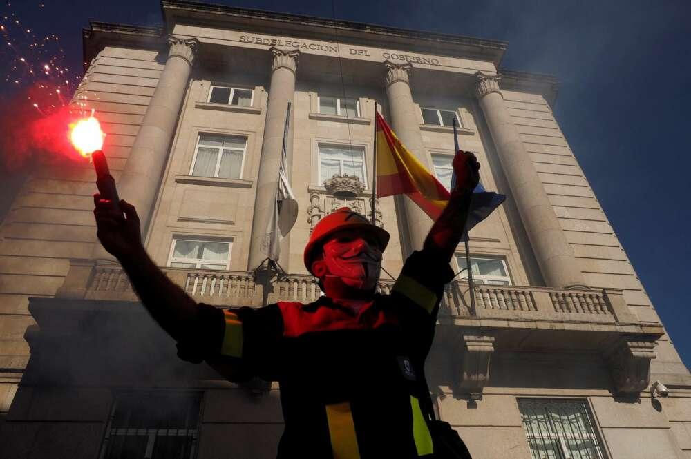 Un manifestante con una bengala delante de la subdelegación del Gobierno, durante la protesta convocada por los trabajadores de Alcoa San Cibrao por la viabilidad de la única fábrica de aluminio primario que queda en España bajo el lema 'A loita continúa'. EFE/Eliseo Trigo