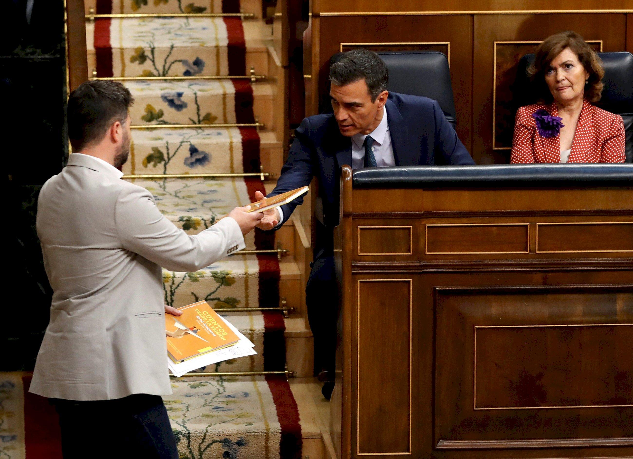 El portavoz de ERC, Gabriel Rufián, de pie, entregando a Sánchez un ejemplar del libro de cuentos escrito por Junqueras en prisión en julio. Foto: EFE/Ballesteros