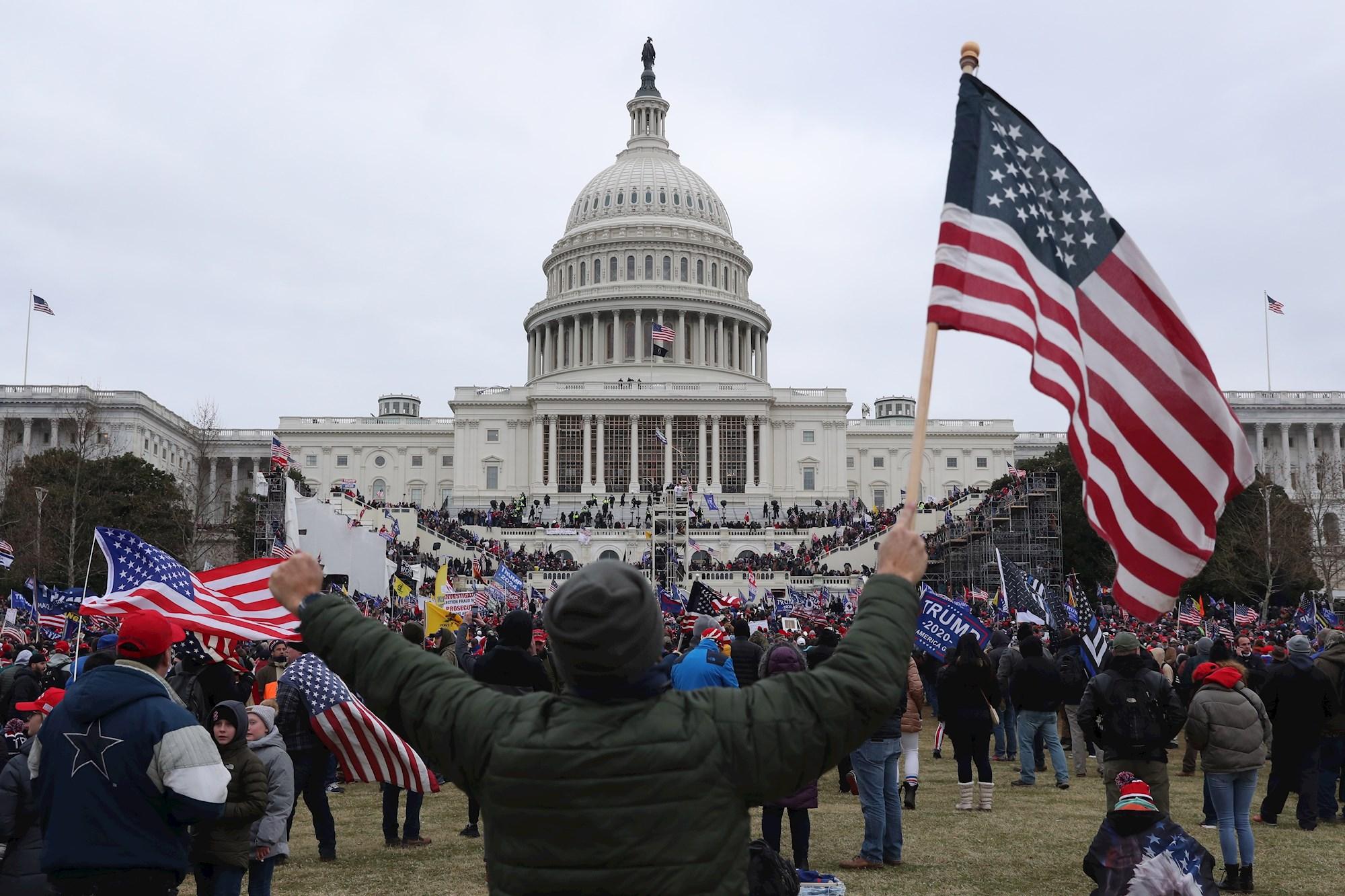 Un seguidor de Donald Trump sostiene la bandera de los Estados Unidos frente al Capitolio estadounidense, el 6 de enero de 2021 | EFE/MR/Archivo
