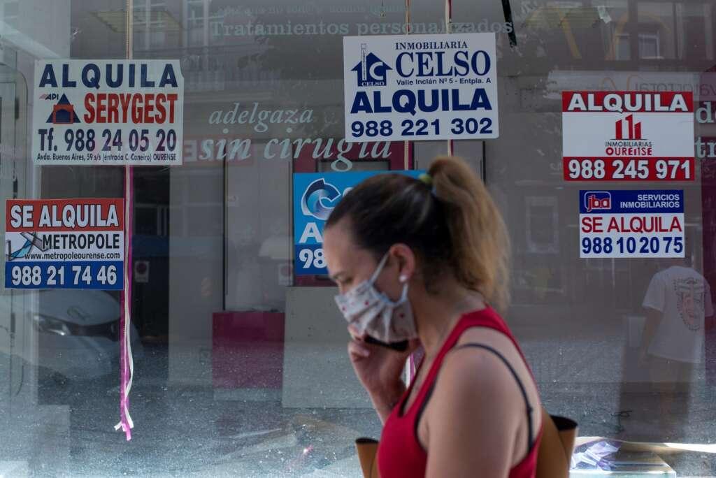 Una mujer con mascarilla pasa ante un comercio cerrado con varios carteles que anuncian su alquiler, el 10 de julio de 2020, en Orense | EFE/BL/Archivo