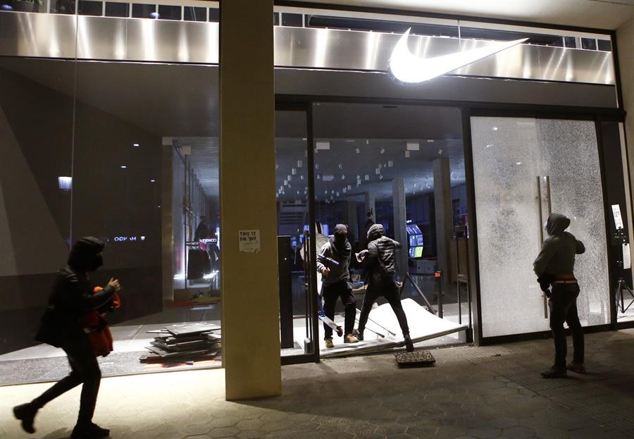 Varios encapuchados entran en un comercio de Barcelona tras la manifestación celebrada esta tarde en protesta por el encarcelamiento del rapero Pablo Hasél. EFE/Quique García