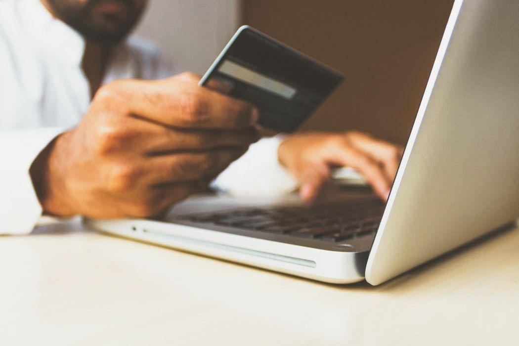 hombre sujetando una tarjeta de credito