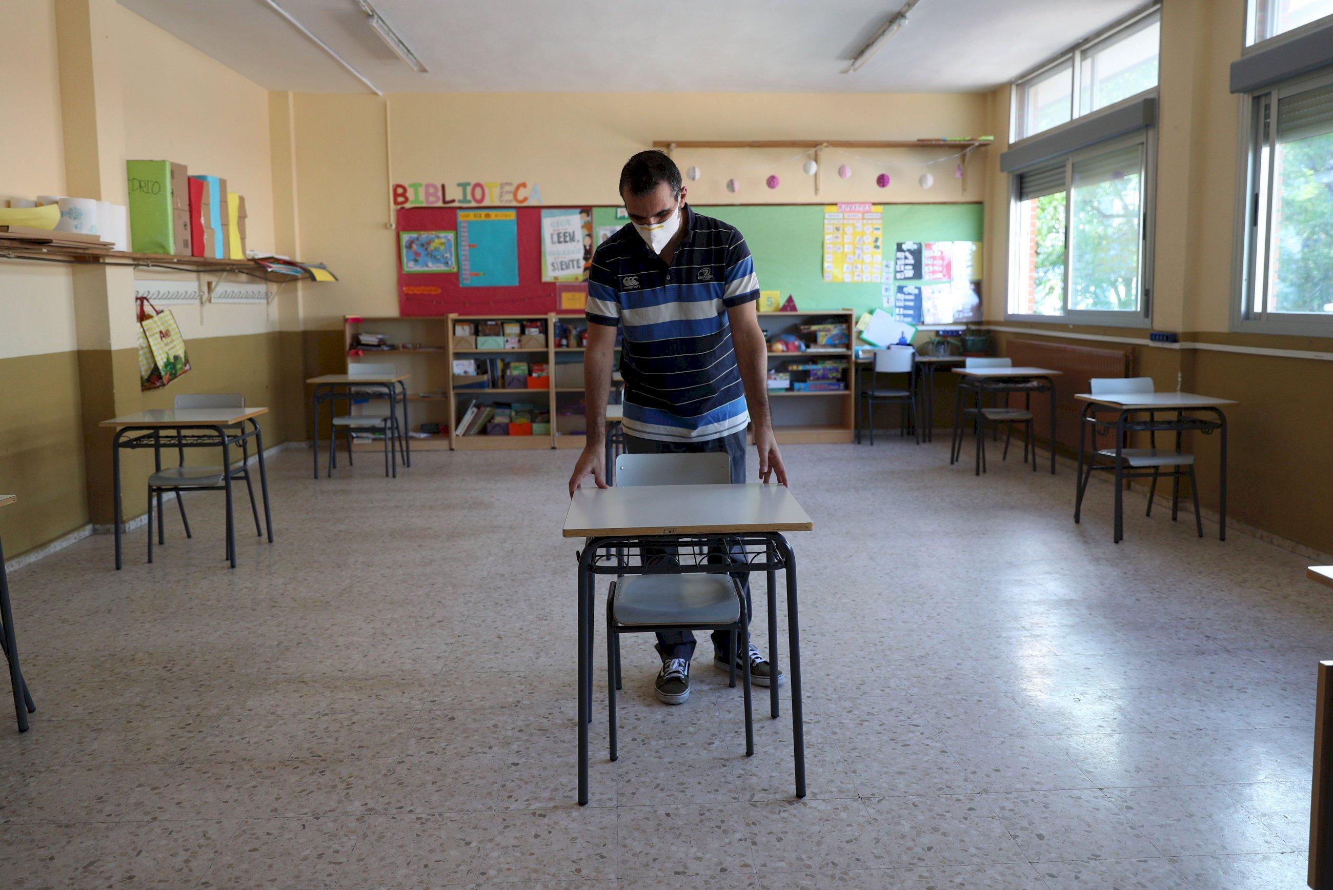 Un profesor coloca las mesas para mantener la distancia de seguridad en el colegio Jaime Vera en el primer día de vuelta voluntaria a las aulas para los niños de primaria de Torrejón de Ardoz, Madrid. EFE