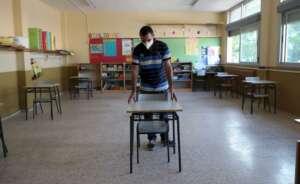 un profesor coloca las mesas para mantener la distancia de seguridad en el coleg