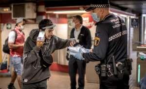 una patrulla de la policia local de valencia reparte mascarillas en un parada de