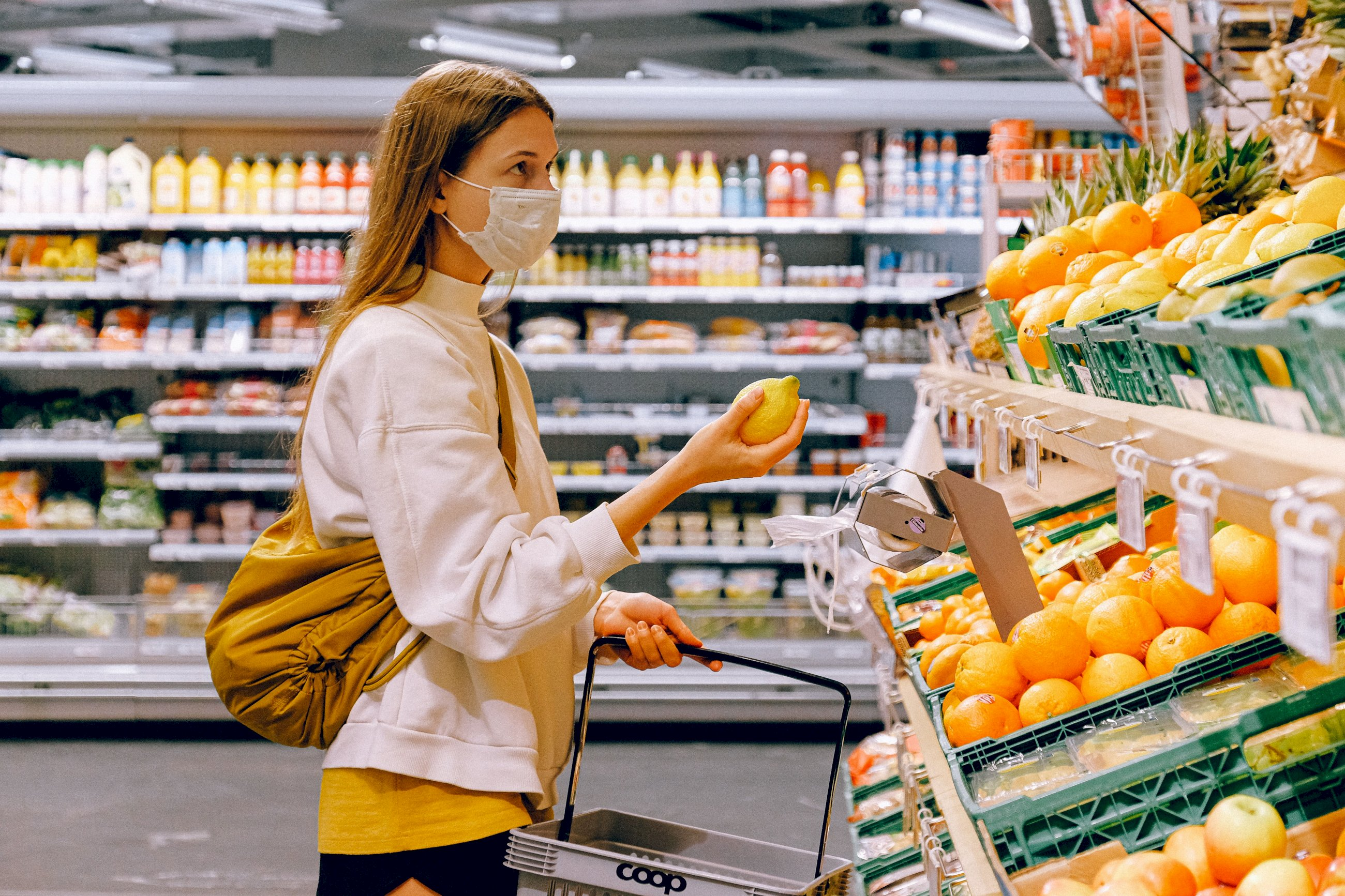 woman in yellow tshirt and beige jacket holding a fruit 3962285