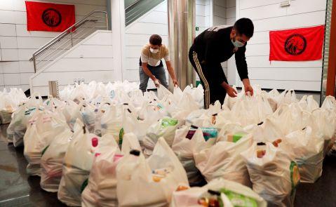 """Dos integrantes de la plataforma integrada por organizaciones sociales """"Esperanza Obrera"""" preparan las bolsas de comida en el edificio ocupado la semana pasada en el centro financiero de la ciudad, para el reparto de alimentos llevado a cabo este lunes. EFE/Kai Försterling"""
