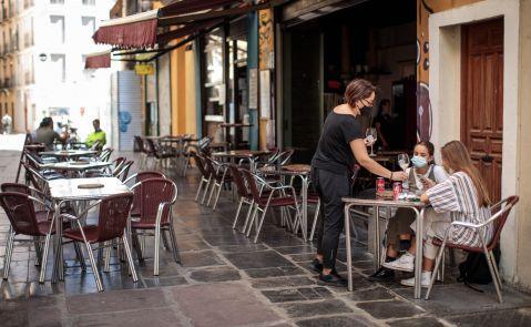 Una camarera atiende una mesa de una terraza en el centro de València. El sector servicios es el más afectado por los ERTE