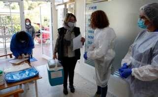 Una trabajadora de la consellería de Sanidad de la generalitat Valenciana, descarga el primer lote de vacunas a su llegada a la residencia Casa Retino El Salvador, en Torrent (Valencia) / EFE