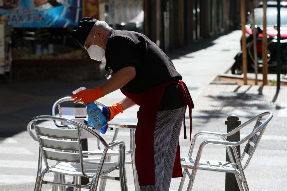 Un camarero limpia las mesas y sillas de una terraza de un bar - Iván Terrón - Europa Press - Archivo