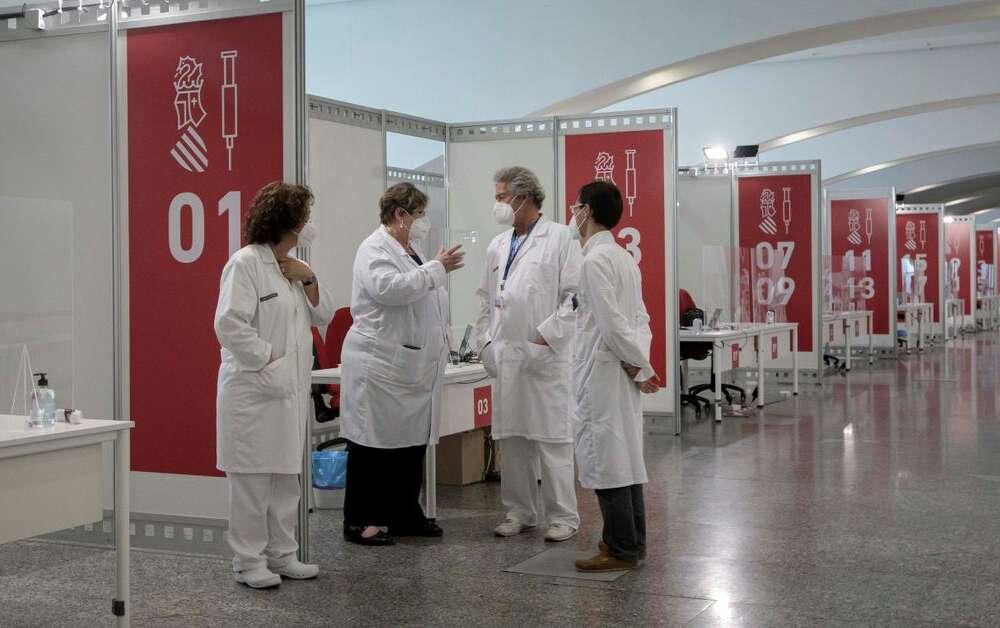 Varios sanitarios conversan este sábado en el punto de vacunación masiva de Valencia situado en la Ciudad de las Artes y las Ciencias. EFE/Biel Aliño