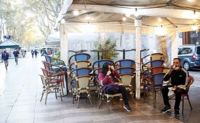 Dos personas sentadas en la terraza de un bar cerrado de las Ramblas de Barcelona, este viernes. EFE/Quique García