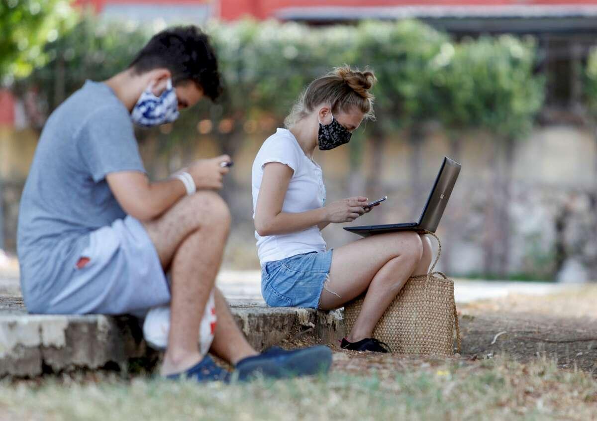 Dos jóvenes conectados a internet desde un parque. Foto: Efe