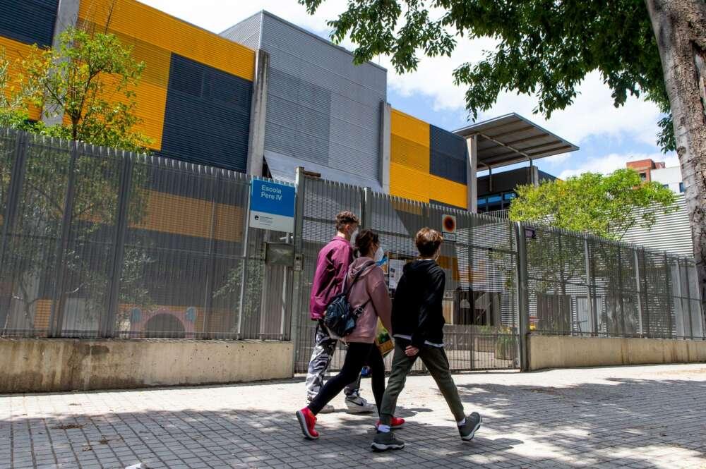 Varios adolescentes pasean frente a una escuela cerrada. Foto: Efe