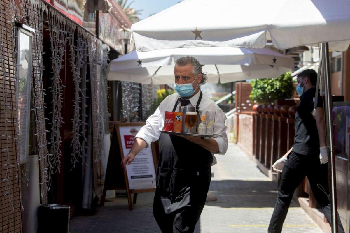 Un camarero lleva su pedido a unos clientes a una de las terrazas del Puerto Olímpico de Barcelona / EFE