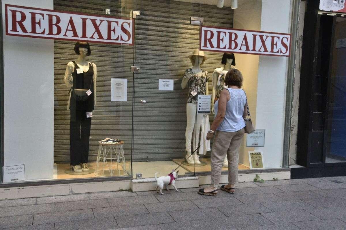 Una mujer observa el escaparate una tienda en rebajas cerrada. Foto: Efe/Ramón Gabriel/Archivo