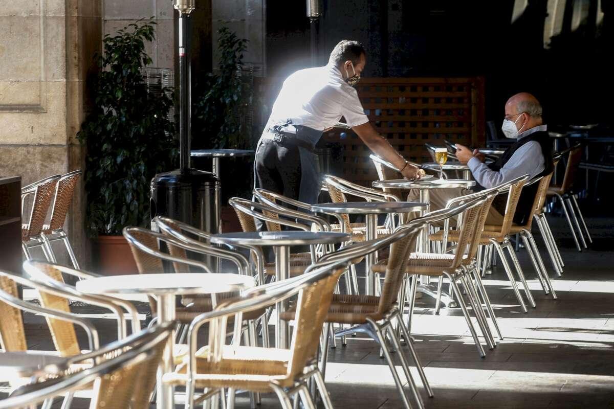Un camarero atiende a un cliente, este miércoles, en un local de la Plaza Real de Barcelona. /EFE/Quique Garcia