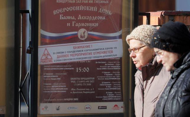 Moscú (Federación de Rusia), 17/03 / 2020.- Las mujeres mayores pasan junto a un póster de la sala de conciertos de la Academia de Música Rusa Gnessin con una pegatina que anuncia la cancelación de eventos debido a la pandemia del coronavirus COVID-19, en