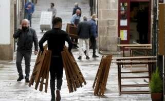 Un camarero monta una terraza en una calle de Santiago de Compostela, uno de los sectores más afectados por la crisis económica en España. EFE/Lavandeira jr