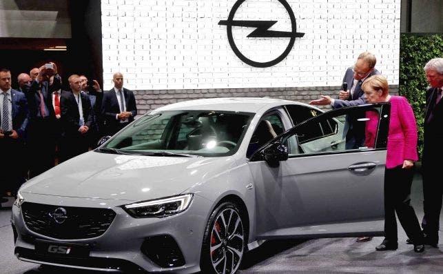 La canciller alemana, Angela Merkel, observa el Opel Insignia GSI junto al primer ejecutivo de Opel Michael Lohscheller.   EFE