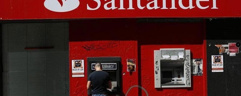 Un cliente saca dinero de un cajero del Banco Santander