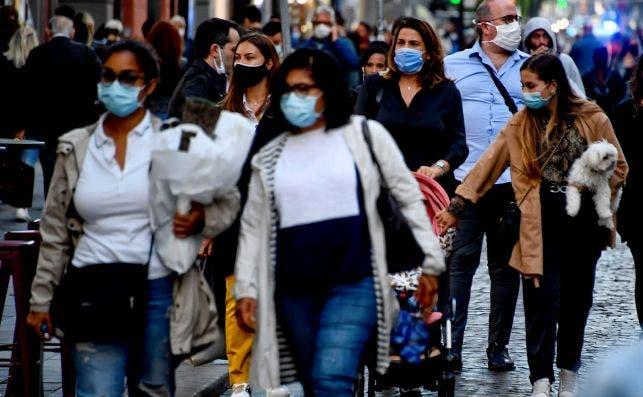 Varios ciudadanos pasean por una calle en Nápoles (Italia) abarrotada de gente, con mascarillas para prevenir la Covid-19 / EFE