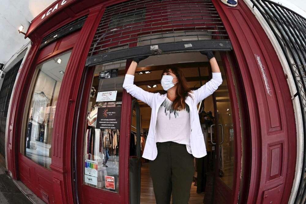 Una mujer abre su negocio. Foto: EFE
