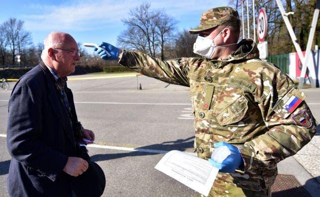 Un soldado esloveno prueba la temperatura de un ciudadano como parte de los esfuerzos para contener el coronavirus, el 17 de marzo de 2020 | EFE/EPA/IK