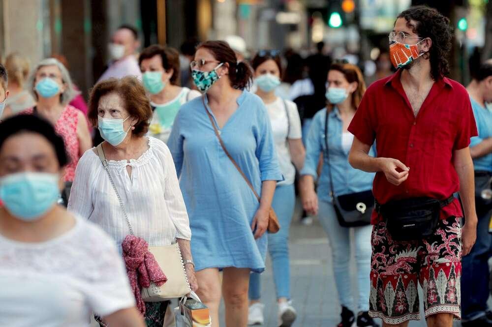 Varias personas pasean de compras por una calle llena de comercios tras la pandemia del coronavirus./ EFE