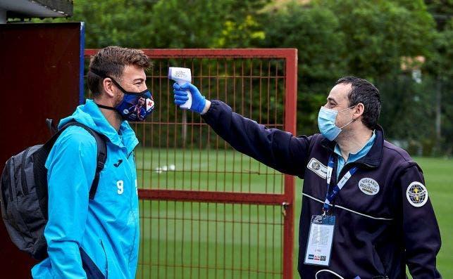 Un miembro de la seguridad del Eibar toma la temperatura al futbolista Sergi Enrich. EFE