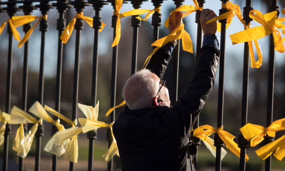 Un hombre coloca lazos amarillos en una calle de Barcelona | EFE/MP/Archivo