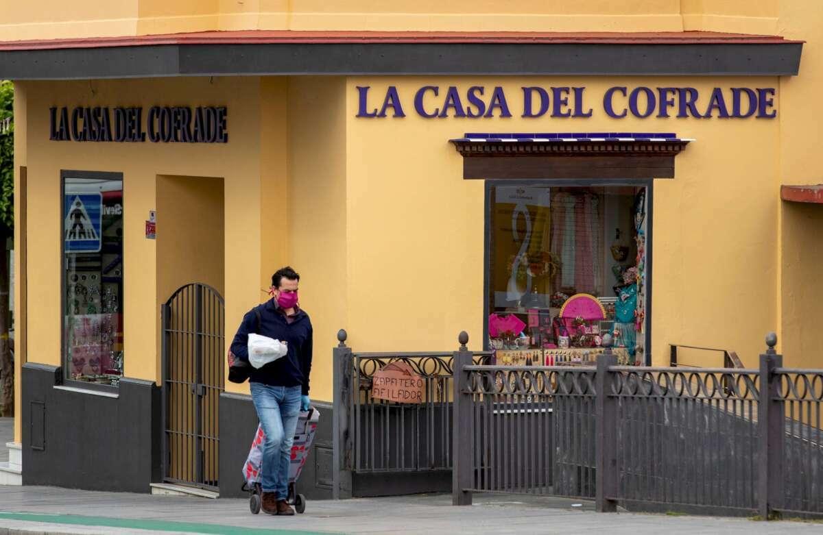 Un hombre protegido con mascarilla camina con un carrito de la compra ante un comercio cerrado de artículos cofraderos en el sevillano barrio de Triana. Foto: Efe