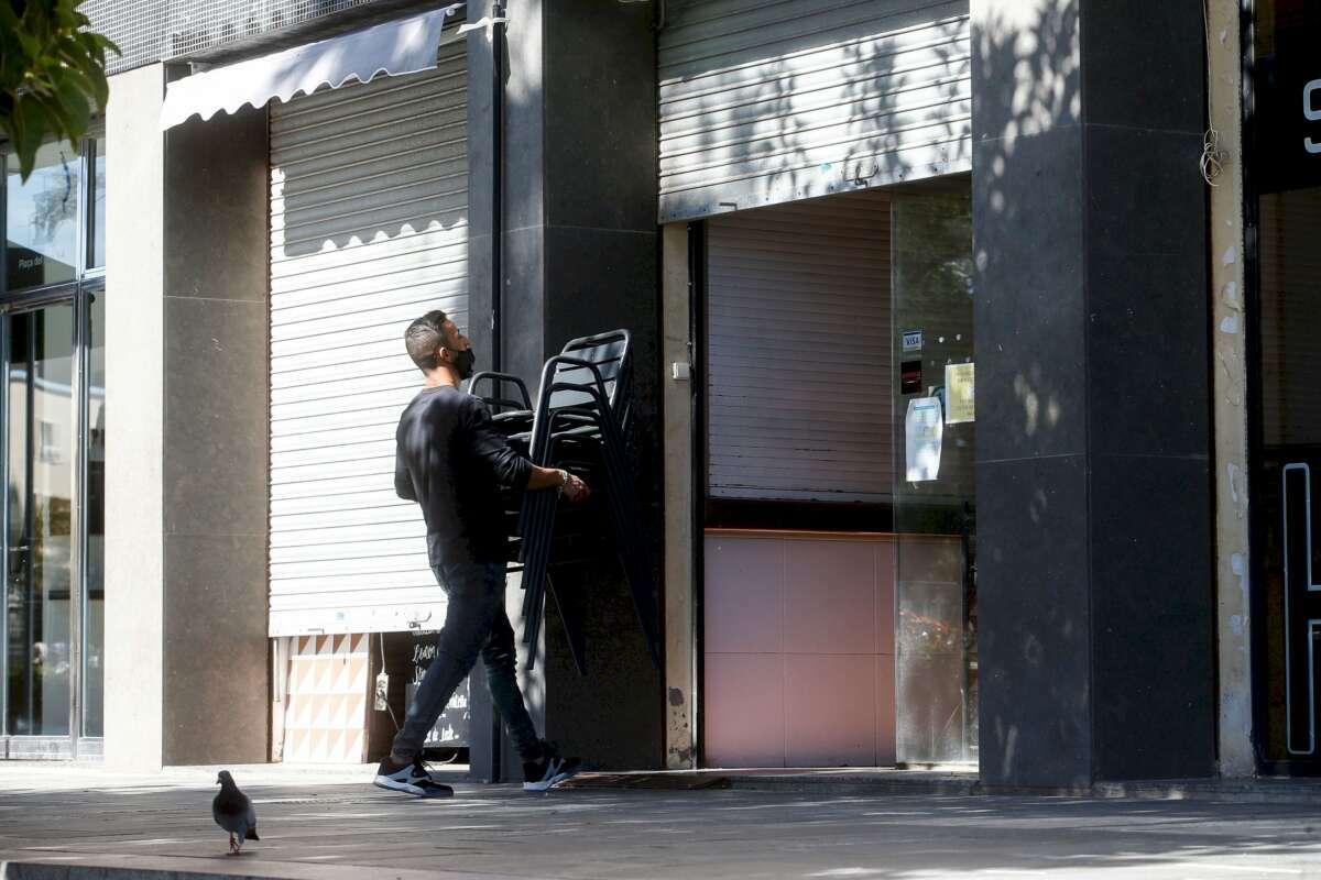 Un camarero recoge las sillas de una terraza de un restaurante del barrio de la Barceloneta de Barcelona. EFE/Quique García