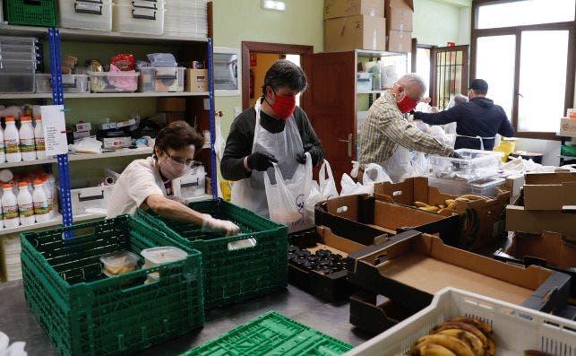 Voluntarios de la Cocina Económica de Oviedo preparan bolsas con el menú de comida y cena para entregar a las familias más necesitadas. EFE/J.L. Cereijido