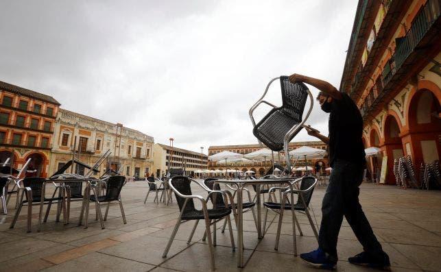 Un trabajador de un bar prepara la terraza en Córdoba el 25 de octubre de 2020. Andalucía sopesa el confinamiento perimetral pero aún no ha tomado la decisión | EFE/Salas/Archivo