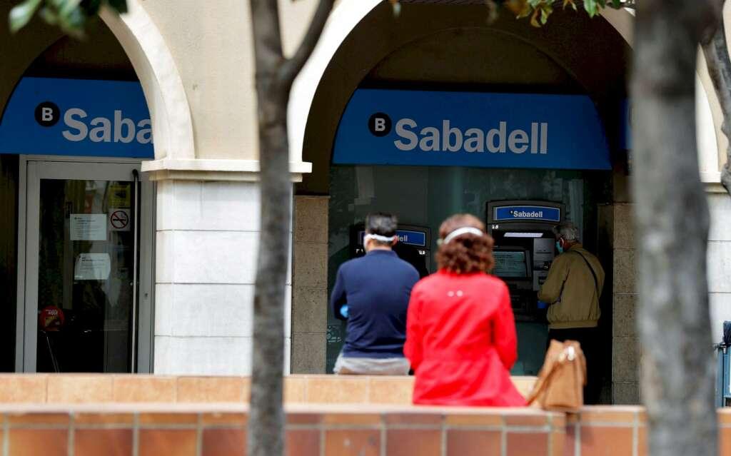 Varias personas esperan ante una sucursal de un banco que mantienen sus puertas abiertas durante la crisis sanitaria del coronavirus. EFE/Manuel Bruque