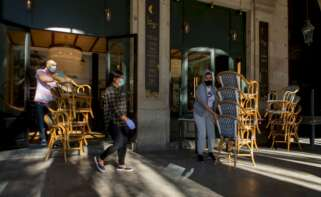 Dos trabajadores recogen la terraza de un bar del centro de Barcelona, afectado por las restricciones sanitarias del coronavirus /EFE/Enric Fontcuberta