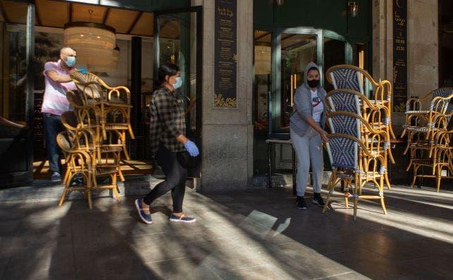 Dos trabajadores recogen la terraza de un bar del centro de Barcelona. Todos los bares y restaurantes de Cataluña permanecen cerrados por orden de la Generalitat. /EFE/Enric Fontcuberta