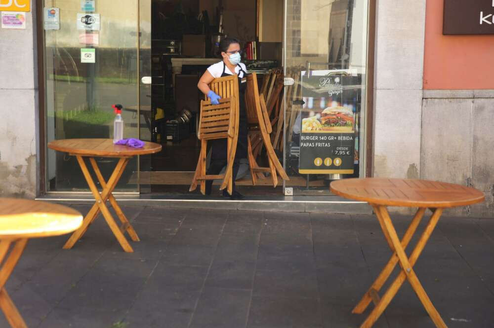 Una trabajadora de un establecimiento de hostelería saca las sillas a la terraza, vacía de clientes por la pandemia de coronavirus. EFE/Archivo