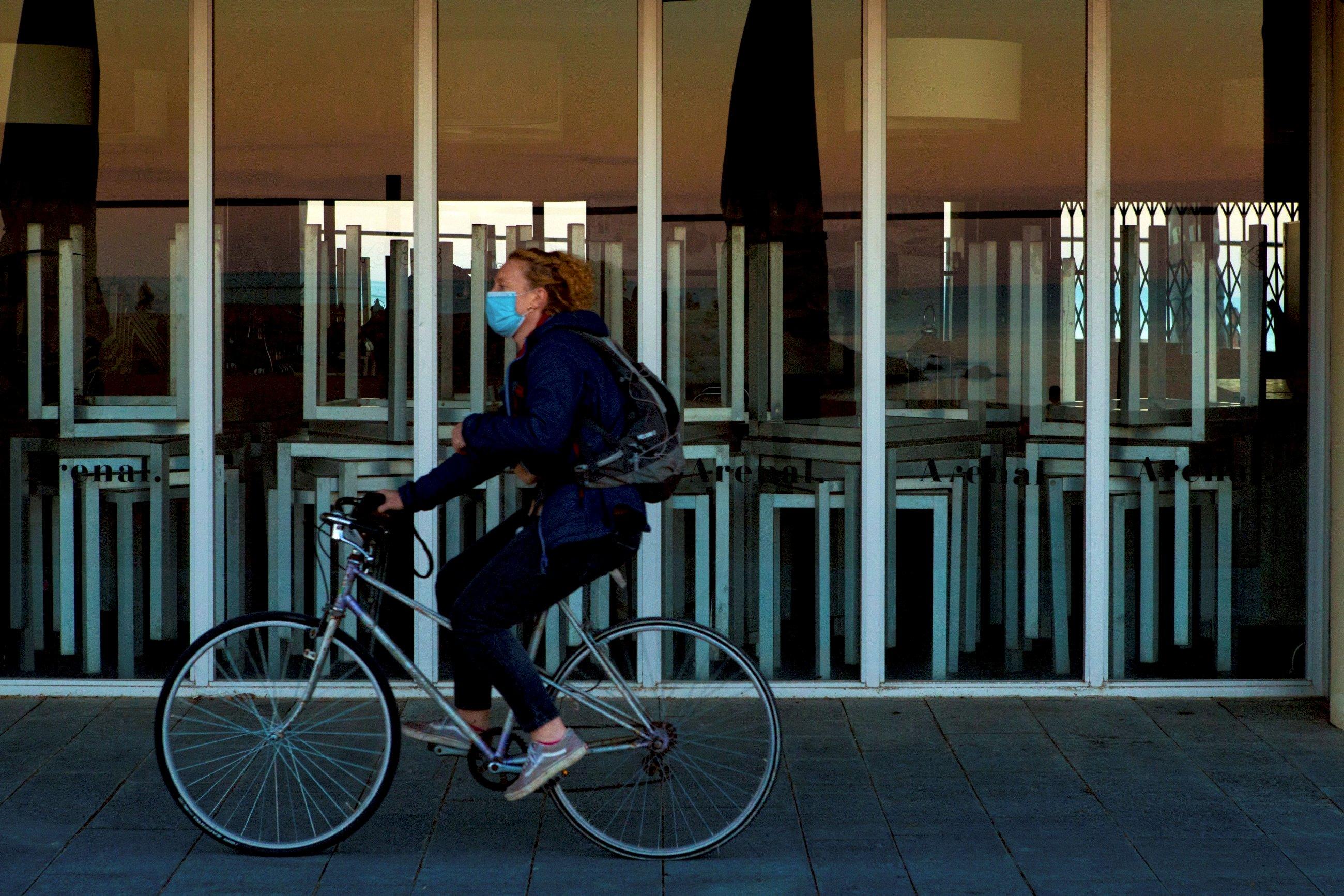 Una mujer pasea en bicicleta con la mascarilla puesta en Barcelona, durante la pandemia de coronavirus de 2020 | EFE/EF/Archivo