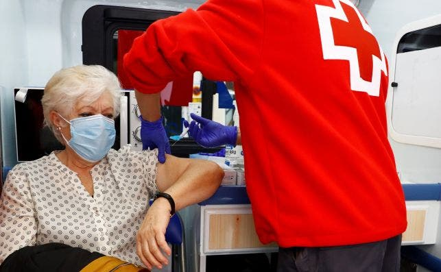 Un miembro de la Cruz Roja vacuna a mujer de la gripe este jueves en la localidad madrileña de Aranjuez / EFE